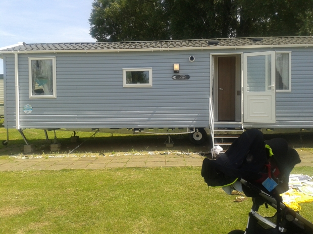 Exterior of our mobile home, Mr Baby parked up under his snooze shade after a walk