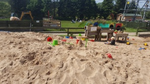The biggest sand pit featuring a tiny toddler